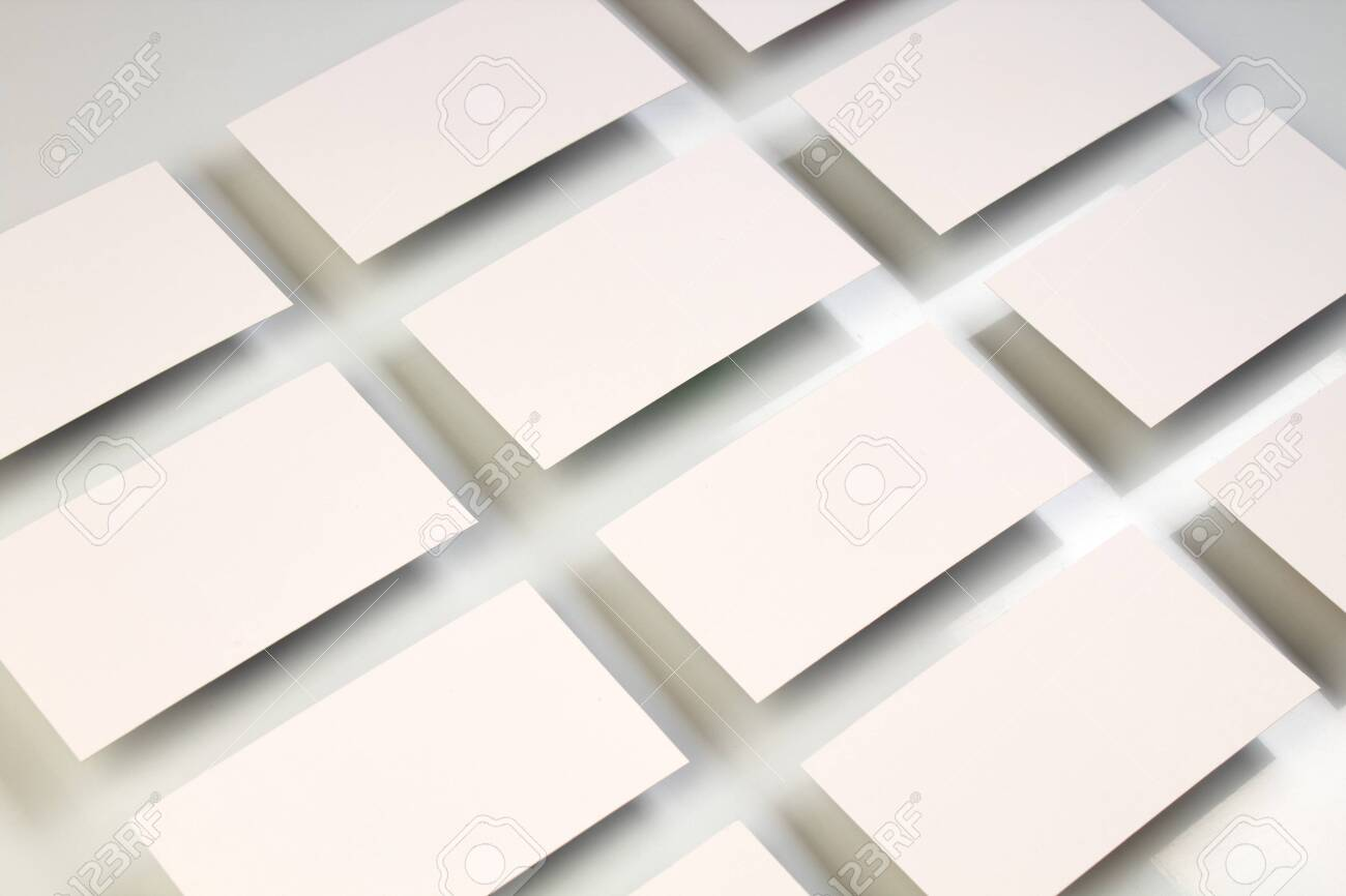 Mockup of horizontal business cards stacks arranged in rows at white textured paper background. - 122962429