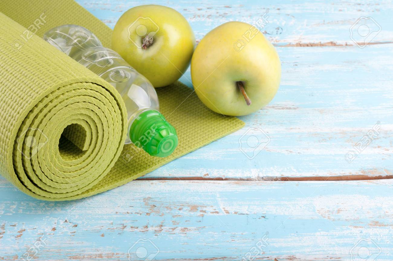 eb07ef67c625a Stock Photo - Yoga mat, bottle of water and apples on a wooden background.  Equipment for yoga. Concept healthy lifestyle, diet and sport. Copyspace.