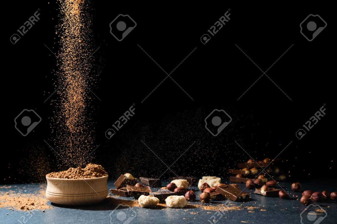 Cocoa powder in motion. Chocolate dust, cacao products, nuts on black background. Copy space - 115146935