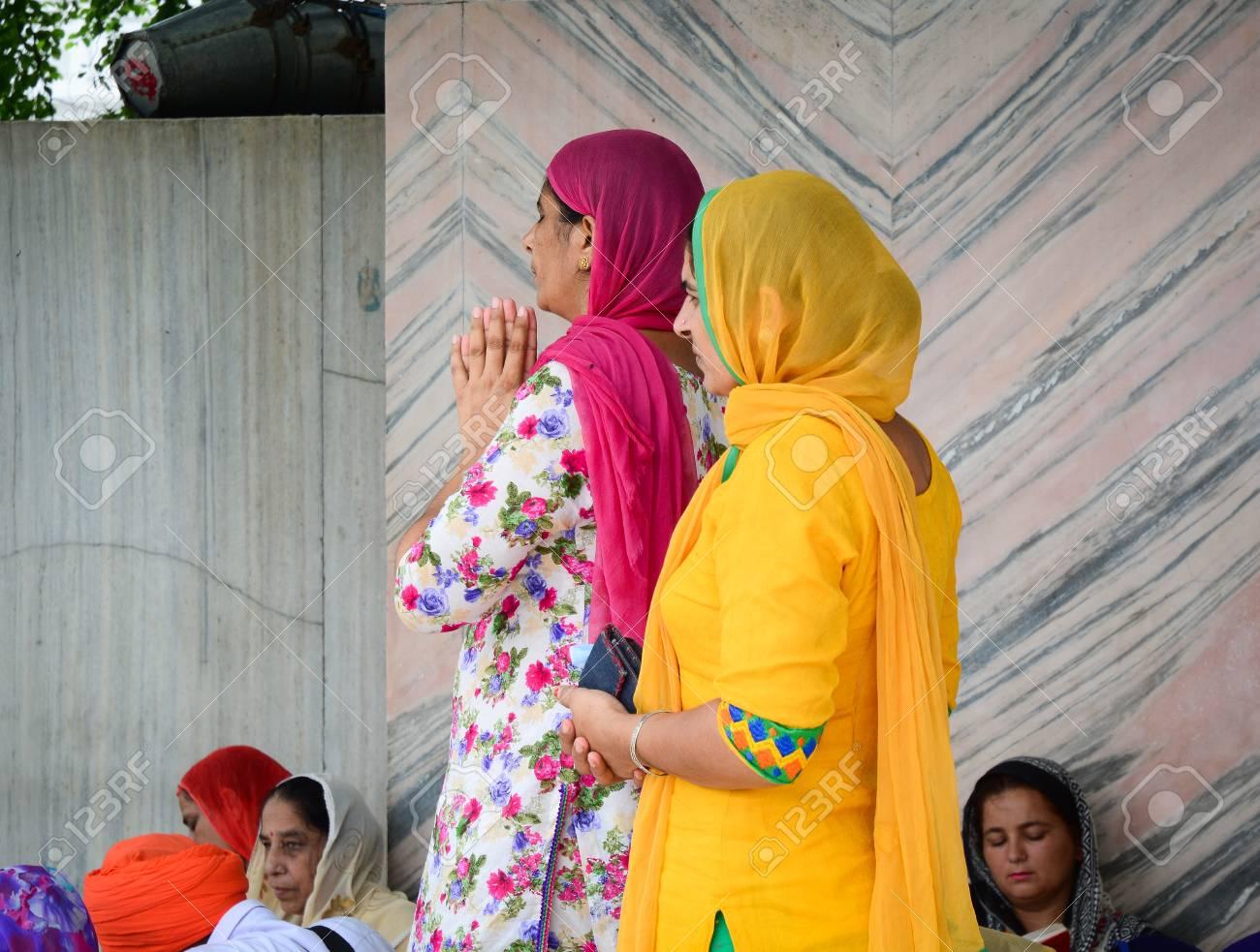Amritsar, India - Jul 25, 2015  Women praying at the Golden Temple