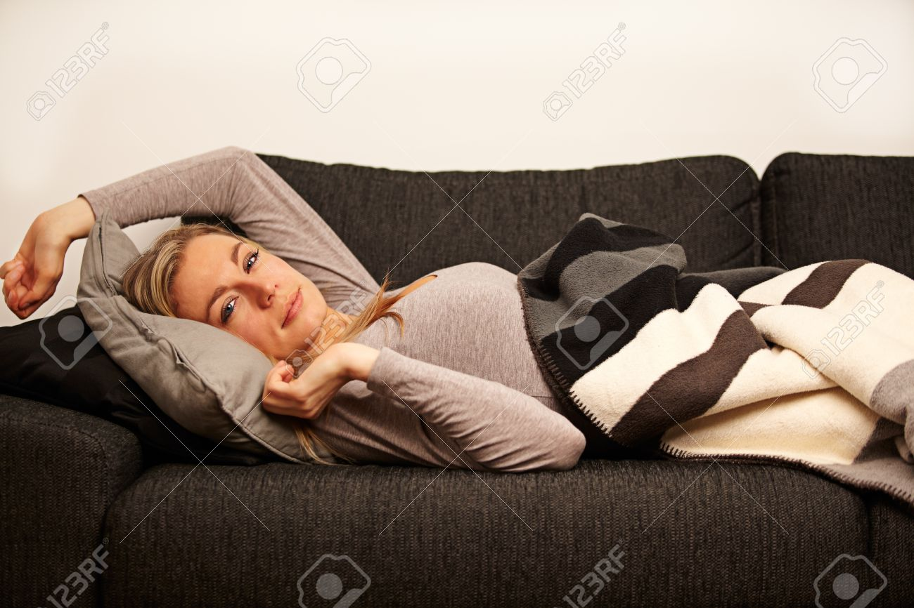 Beautiful sleepy woman just waking up and stretching under cover of a blanket on a sofa Stock Photo - 17458039