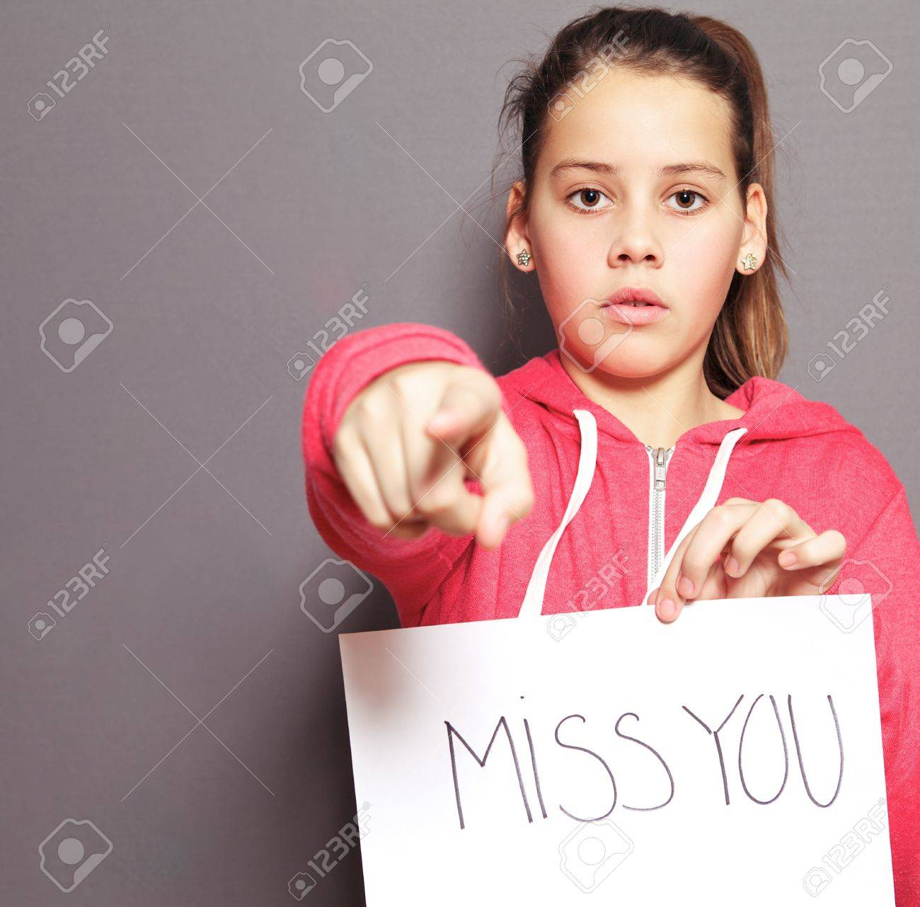 Cute young girl with a doleful expression holding up a sheet of paper with a handwritten MISS YOU and pointing her finger towards the camera, studio portrait on grey Stock Photo - 17495006