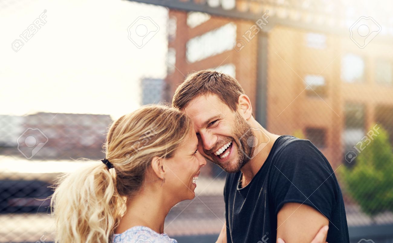 Happy spontaneous attractive young couple share a good joke laughing uproariously and hugging each other outdoors in an urban environment Stock Photo - 45029829