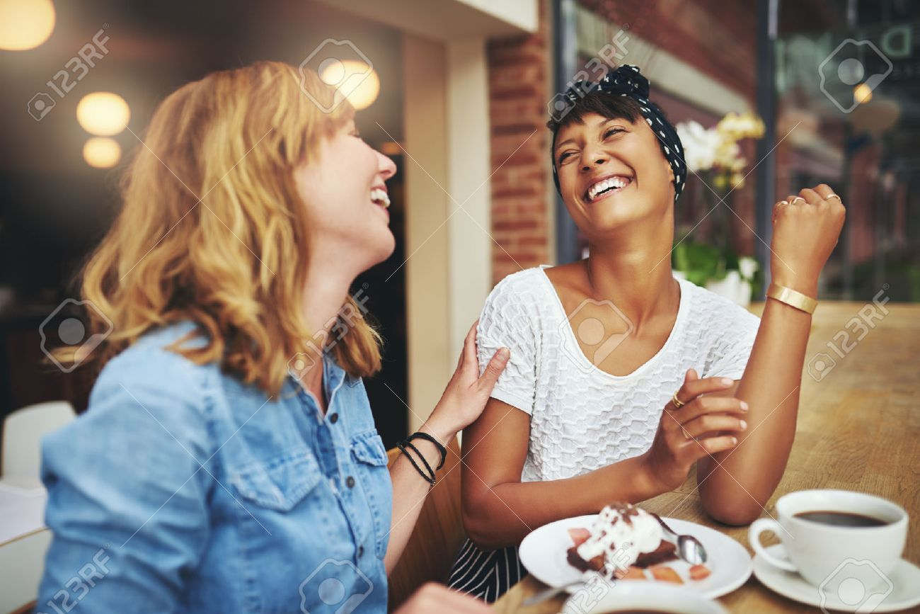 Two multiethnic young female friends enjoying coffee together in a restaurant laughing and joking while touching to display affection - 46626116