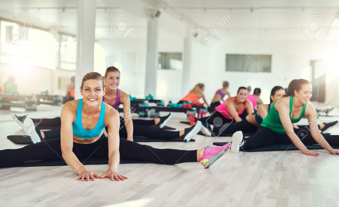 Group of fit women stretching and exercising in a fitness class, aerobics and fitness concept Stock Photo - 47171014