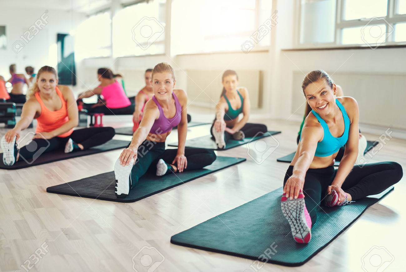 group of young women in aerobics class at a gym doing stretching