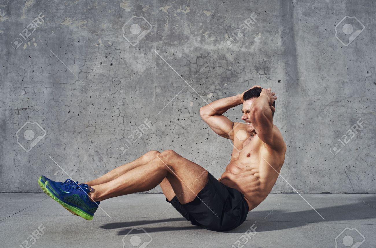 Fitness model exercising sit ups and crunches. Muscular well build, toned body with six pack sweating. Copy space Stock Photo - 47171058