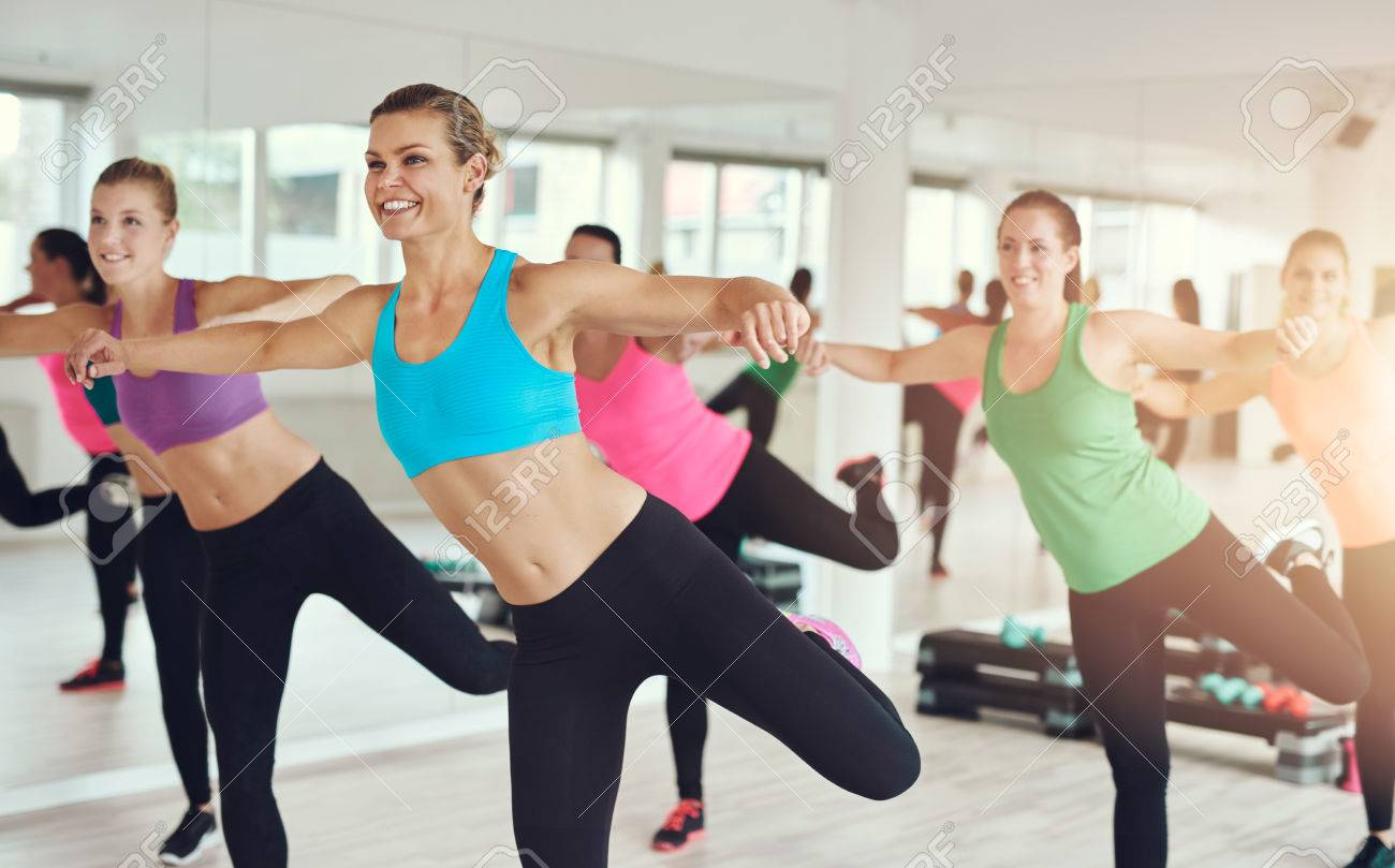 young women in colorful sportswear working out in aerobics class