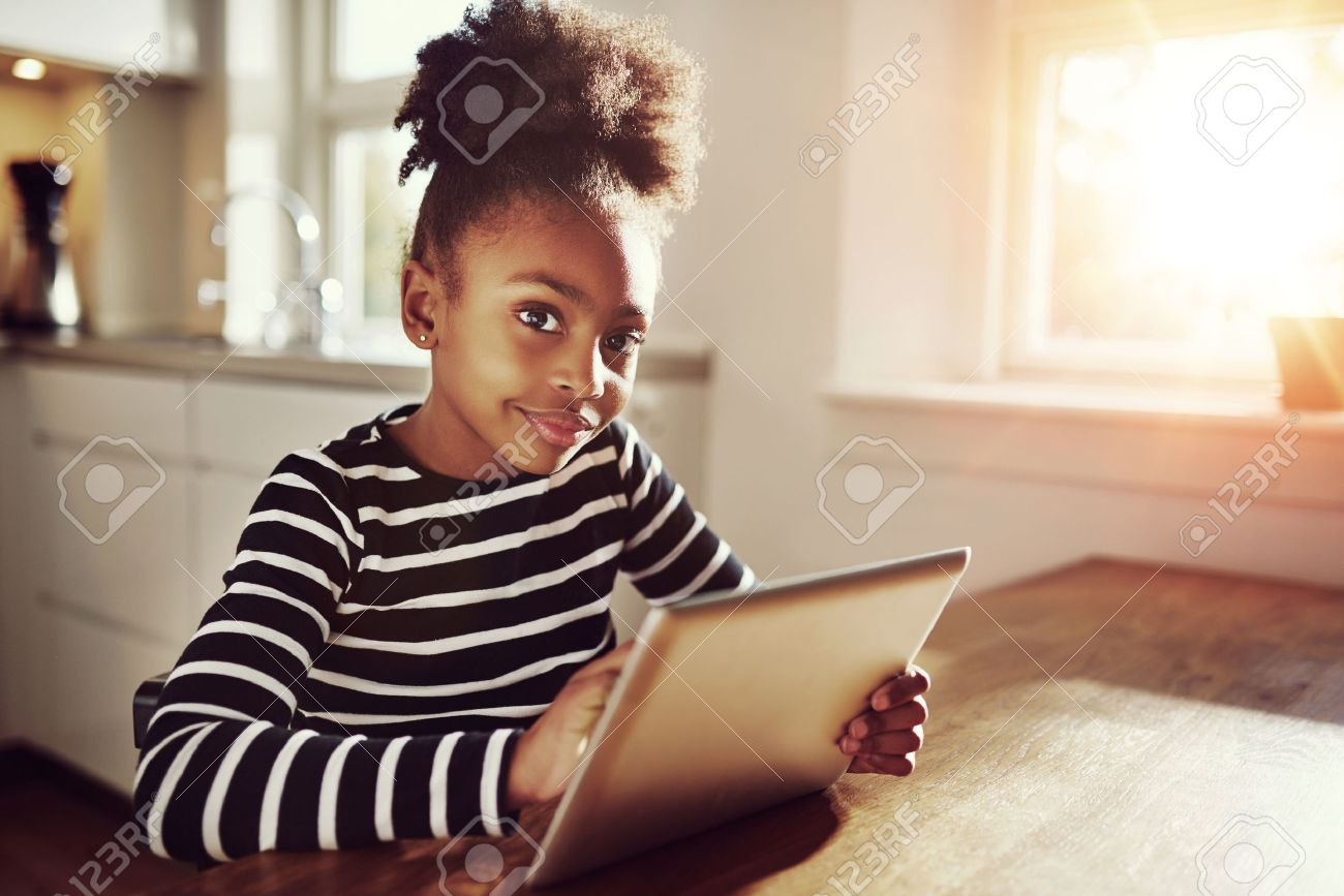 Thoughtful young black girl sitting watching the camera with a pensive expression as she browses the internet on a tablet computer at home - 50386553