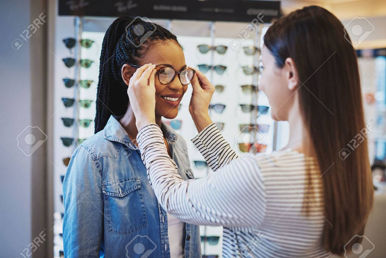 Smiling young African American woman selecting a pair of frames for her glasses being assisted by an optometrist in the store - 56715936