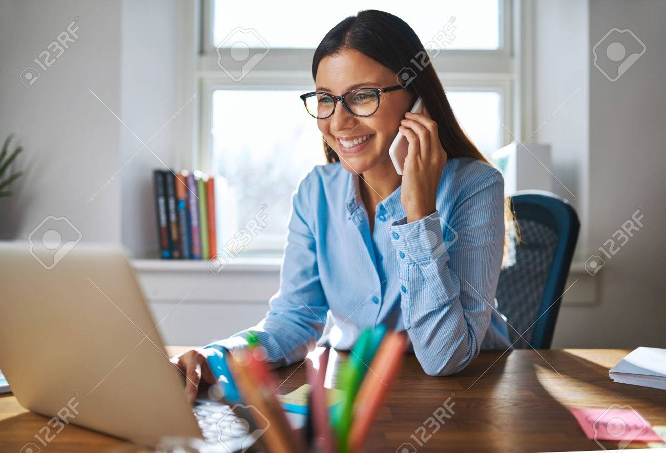 Single happy female business owner with smile and eyeglasses on phone and working on laptop computer at desk with bright window in background - 54383974