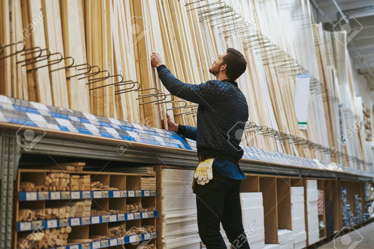 Carpenter selecting lengths of cut wood of a rack in a hardware store , low angle rear view from the side - 54384007
