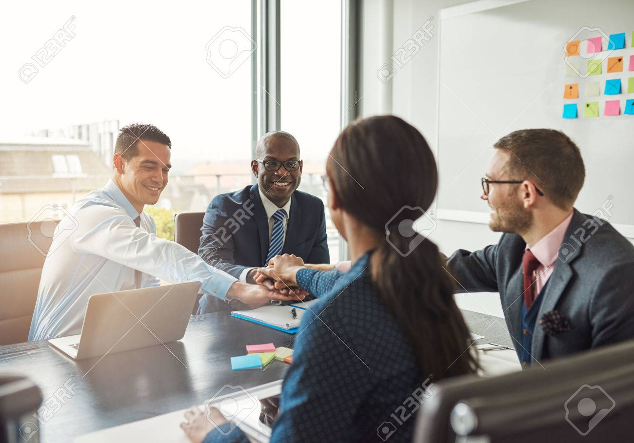 Successful multiracial business team working together affirm their commitment by linking hands across an office table during a meeting - 54827554