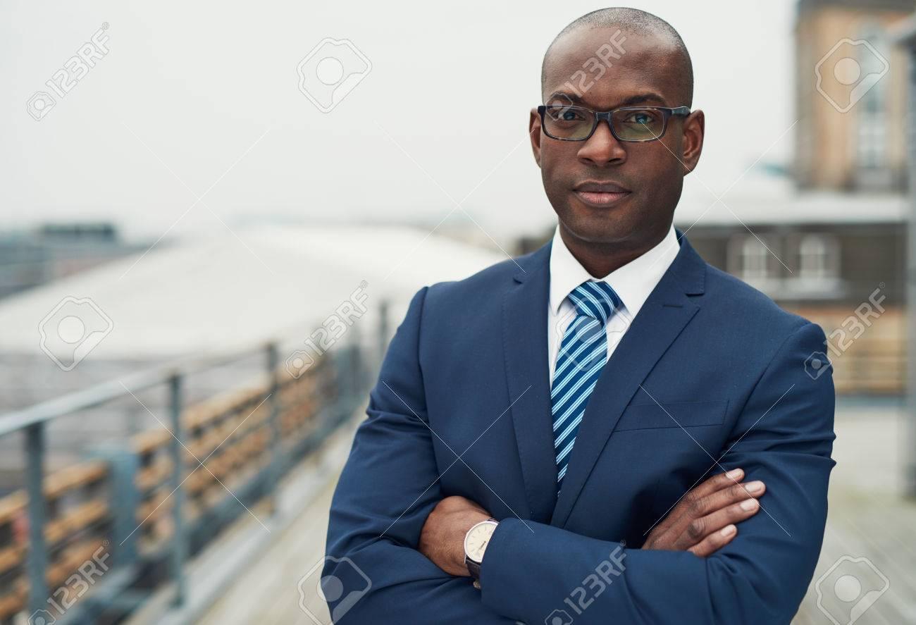 58cdf17bf90e3b Banque d images - Confiant homme d affaires noir dans un costume élégant,  debout avec les bras croisés sur un toit du bloc n de bureau en regardant  la ...