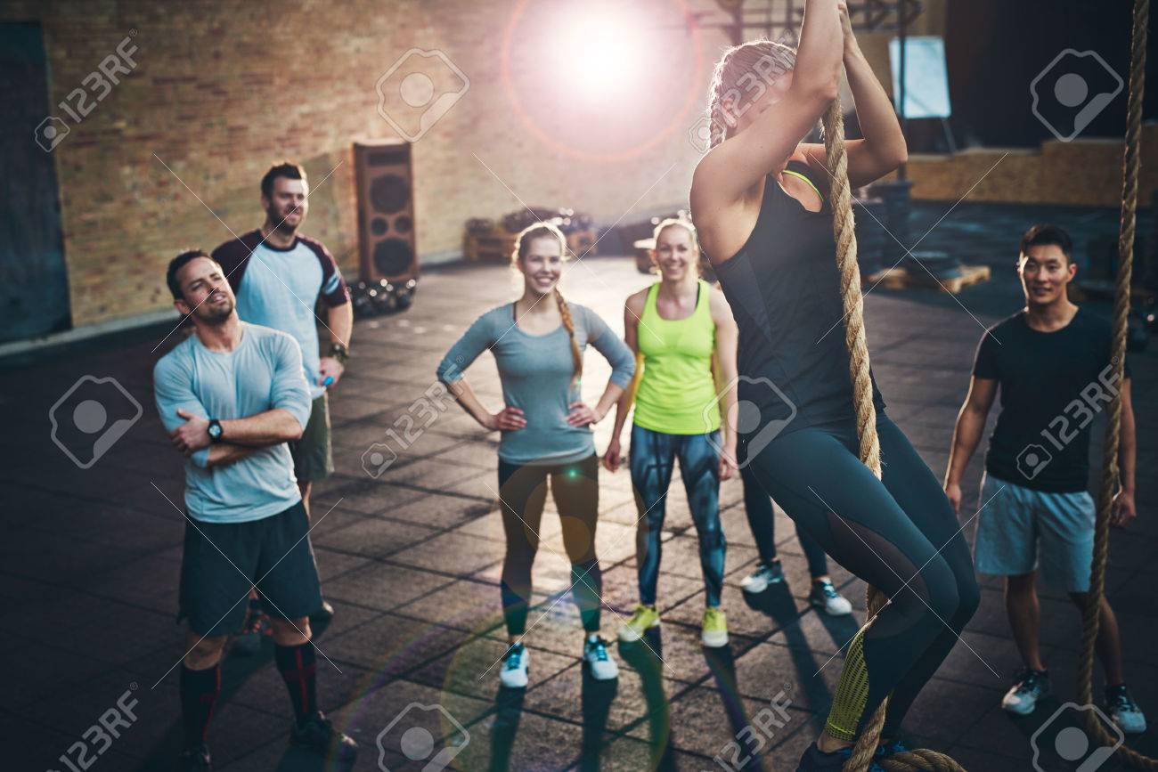 Fit young women climbing a rope in a gym with people on the floor watching - 56414691
