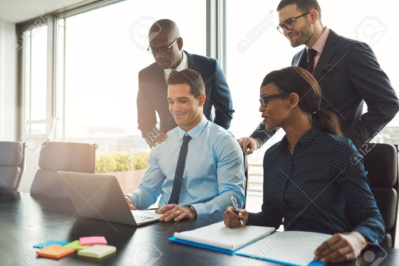 Group of happy diverse male and female business people in formal gathered around laptop computer in bright office - 56414850