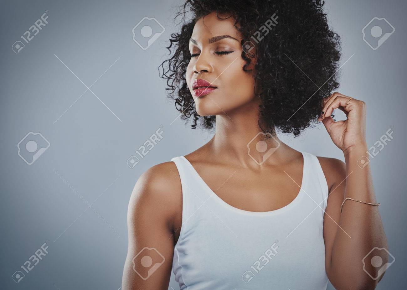 Cropped upper body view of beautiful young African woman looking sideways with closed eyes and fingers touching hair and copy space - 57528906