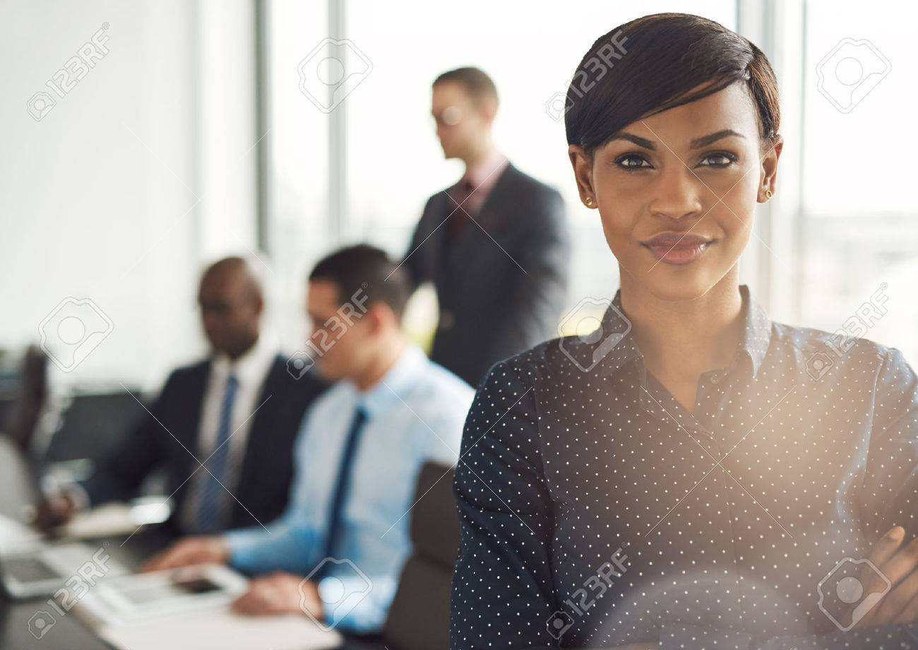 Attractive young grinning business owner in office with polka dot blouse, folded arms and confident expression in front of group of employees at conference table - 58023765