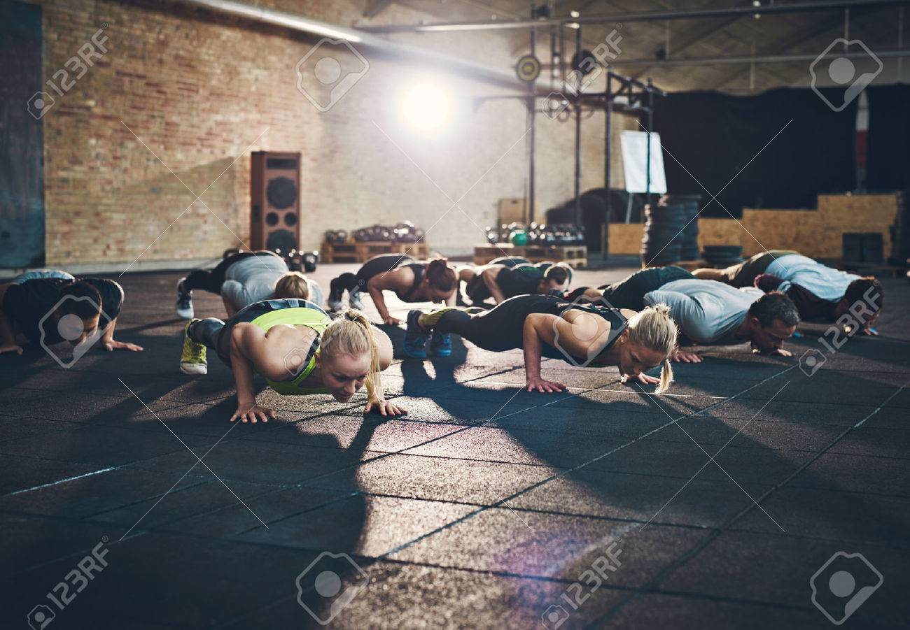 Fit young people doing pushups in a gym looking focused - 58023661