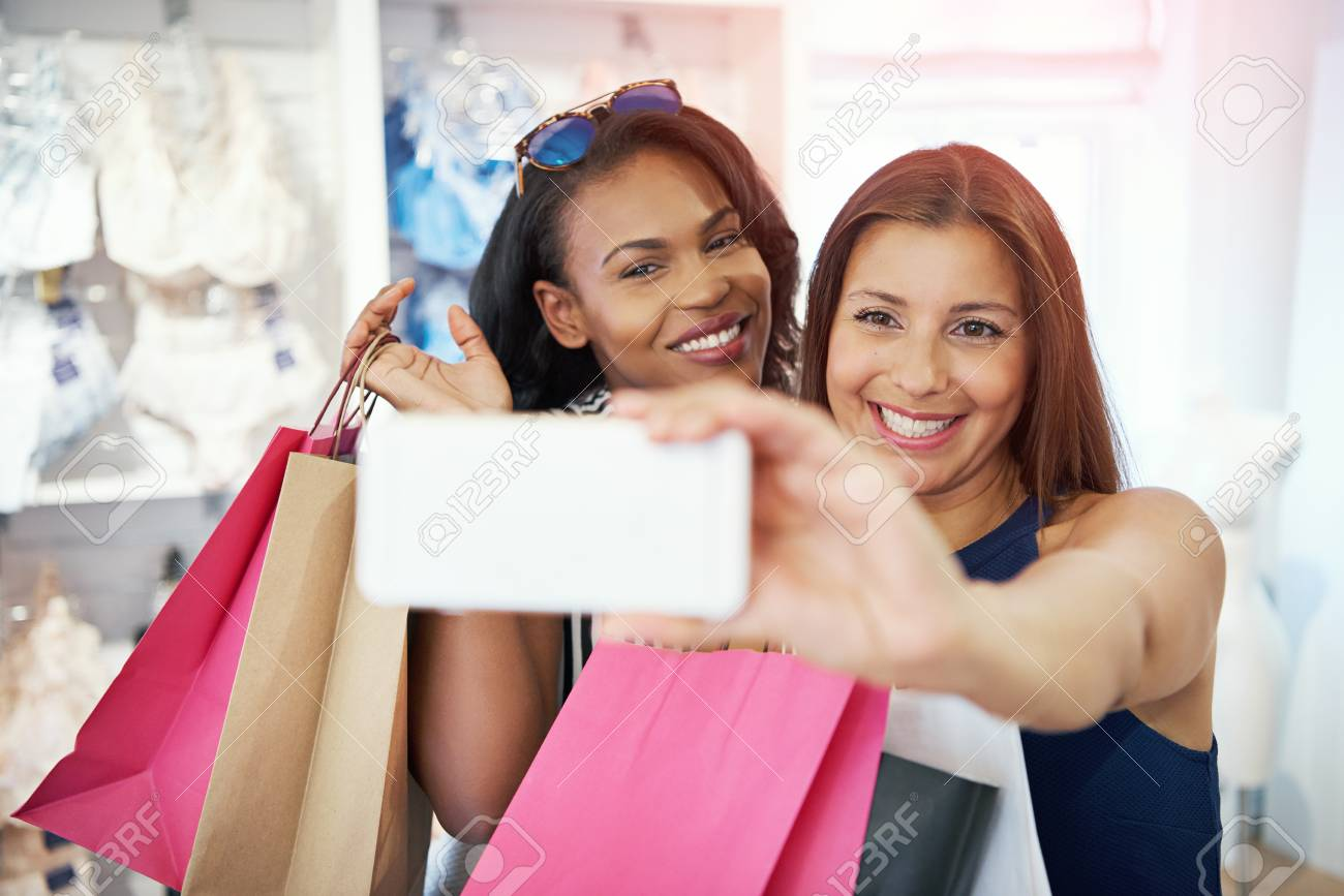 6f5008a4be Happy young women taking a selfie while shopping together in a clothing  store holding their purchases