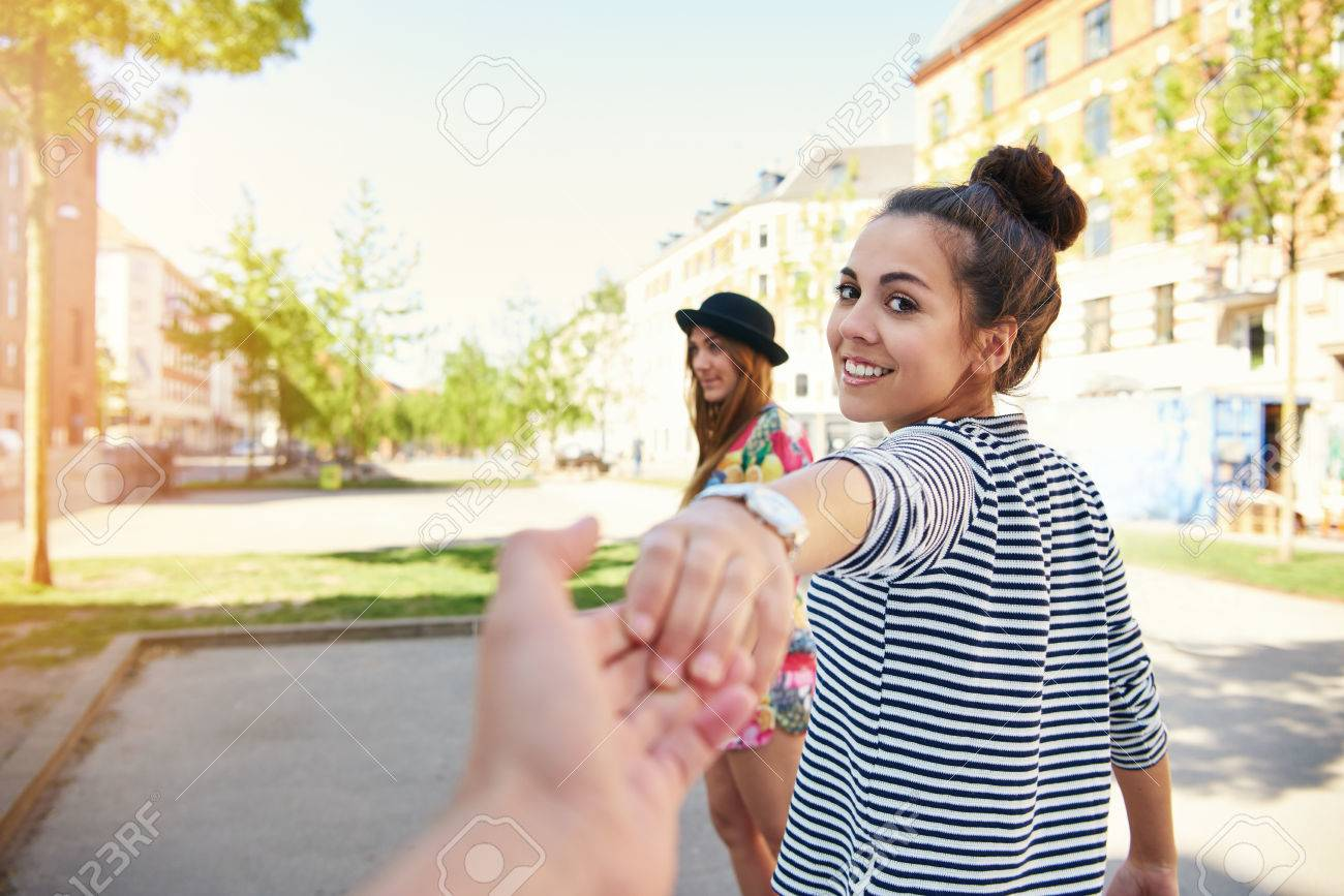 Pretty young woman pulling a man along by the hand turning to look back at him with a happy smile as her friend waits in the background - 62819651
