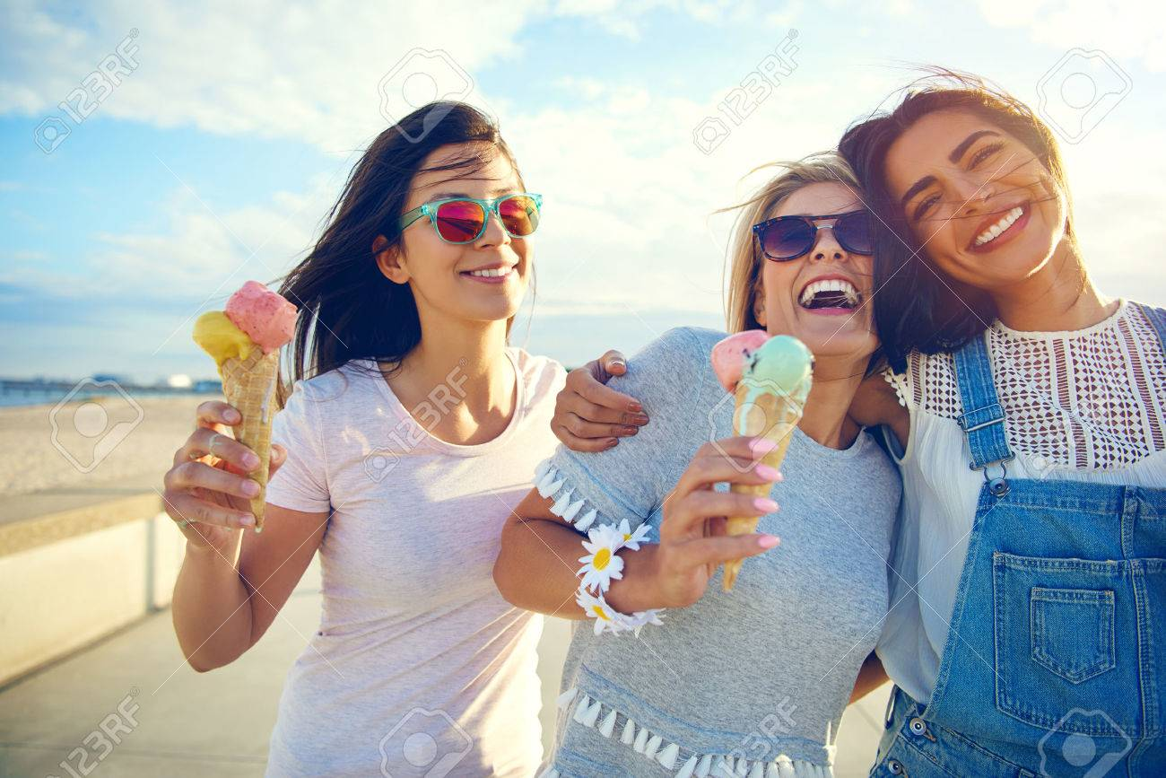 Laughing teenage girls eating ice cream cones as they walk along a beachfront promenade arm in arm enjoying their summer vacation - 63754295