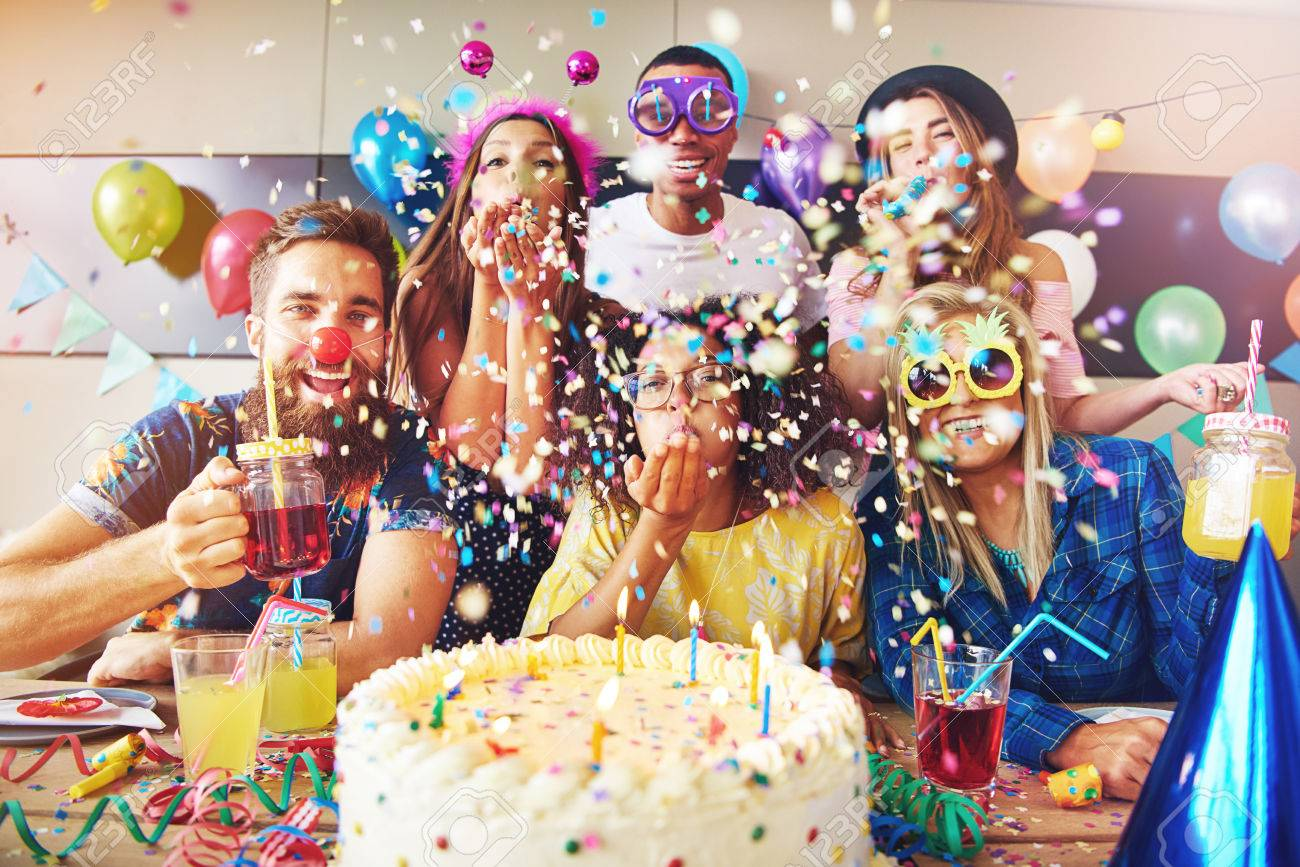 Group of six male and female festive partygoers in front of large white frosting covered cake surrounded by confetti in room - 64785334