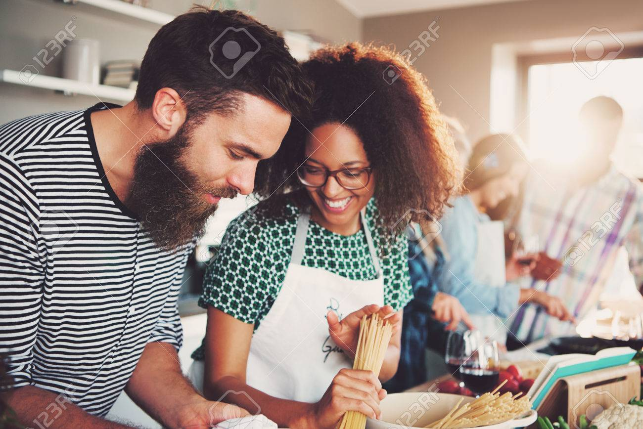 Cute young mixed couple preparing pasta dinner in kitchen with friends. Bright sunlight shining through window. - 65472501