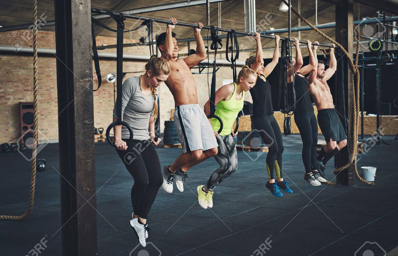Group of six attractive young male and female adults doing pull ups on bar in cross fit training gym with brick walls and black mats - 66830767