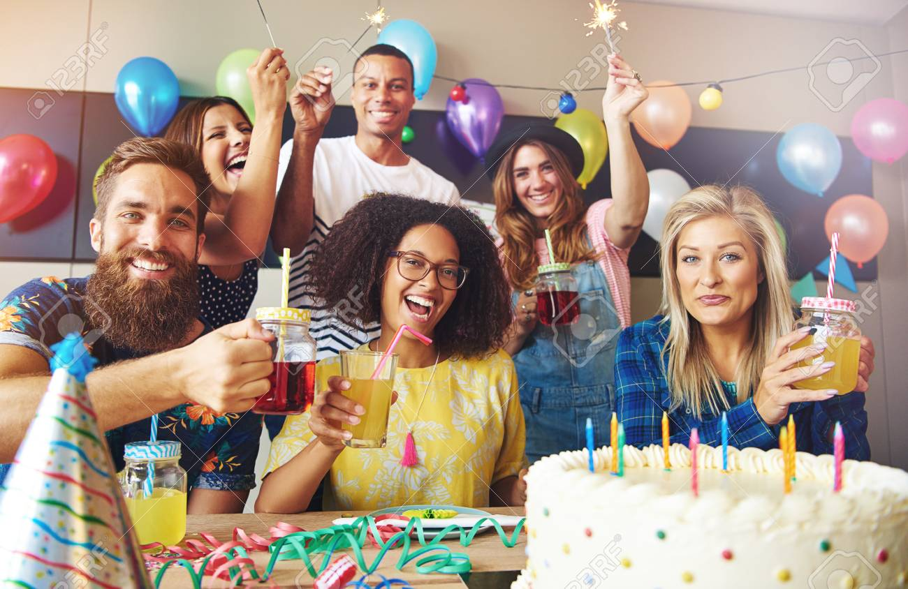 group of six friends holding drinks at birthday celebration in