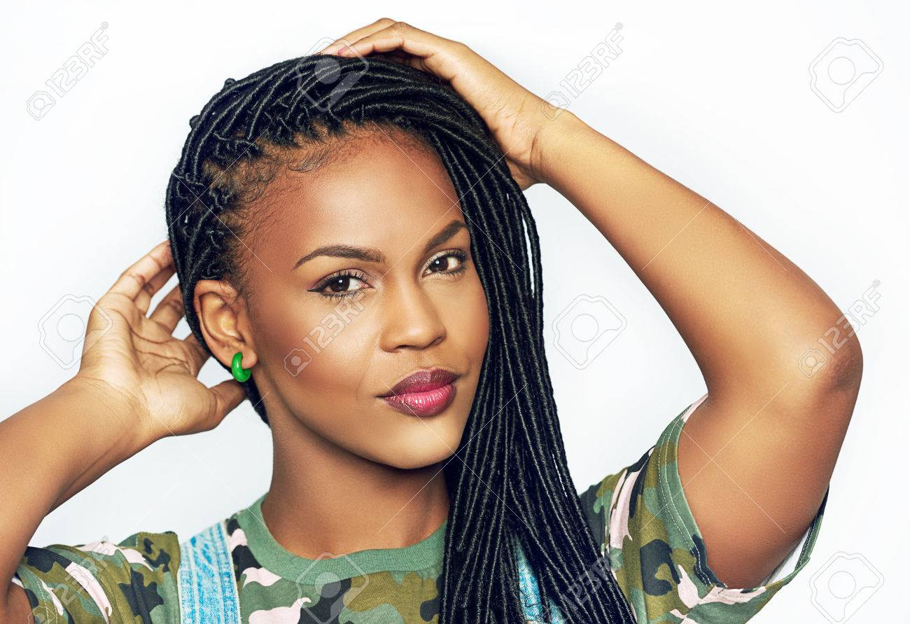 Gorgeous graceful young black African american woman with long braided hair raising her hands to her head as she looks at the camera with a quiet smile - 75315620