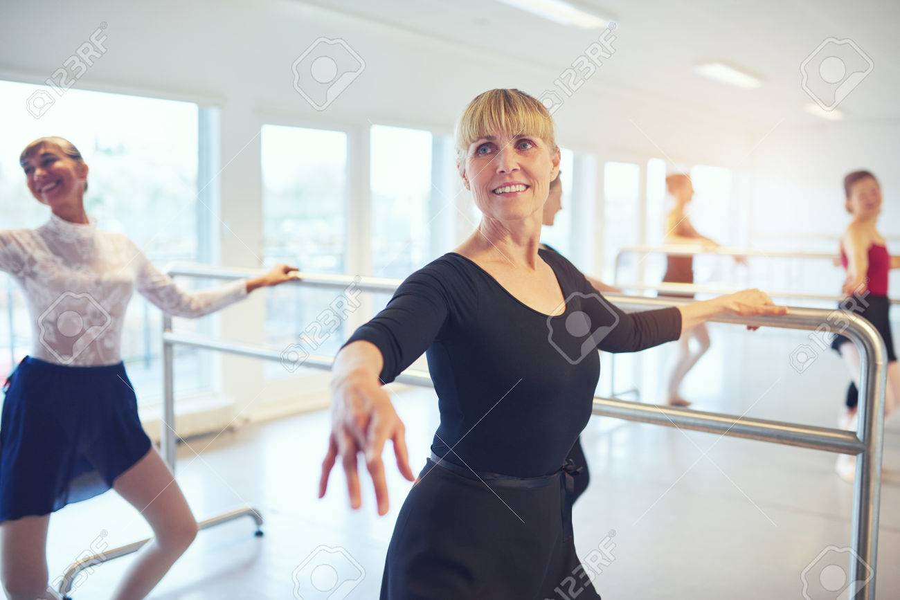 Smiling adult ballerinas standing and doing exercises in ballet..