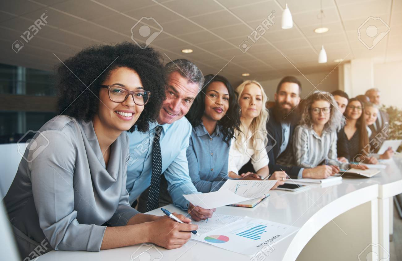 Portrait of a smiling group of diverse corporate colleagues standing in a row together at a table in a bright modern office - 90590836