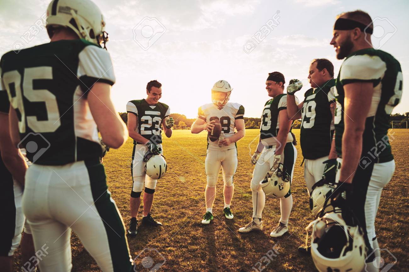 Young American football quarterback discussing offensive plays with his teammates during a practice session outside on a sports field in the afternoon - 109499390