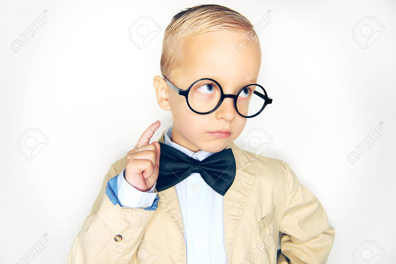 Adorable little blonde boy wearing a suit, bowtie and glasses like a professor pointing up against a white background - 114420625