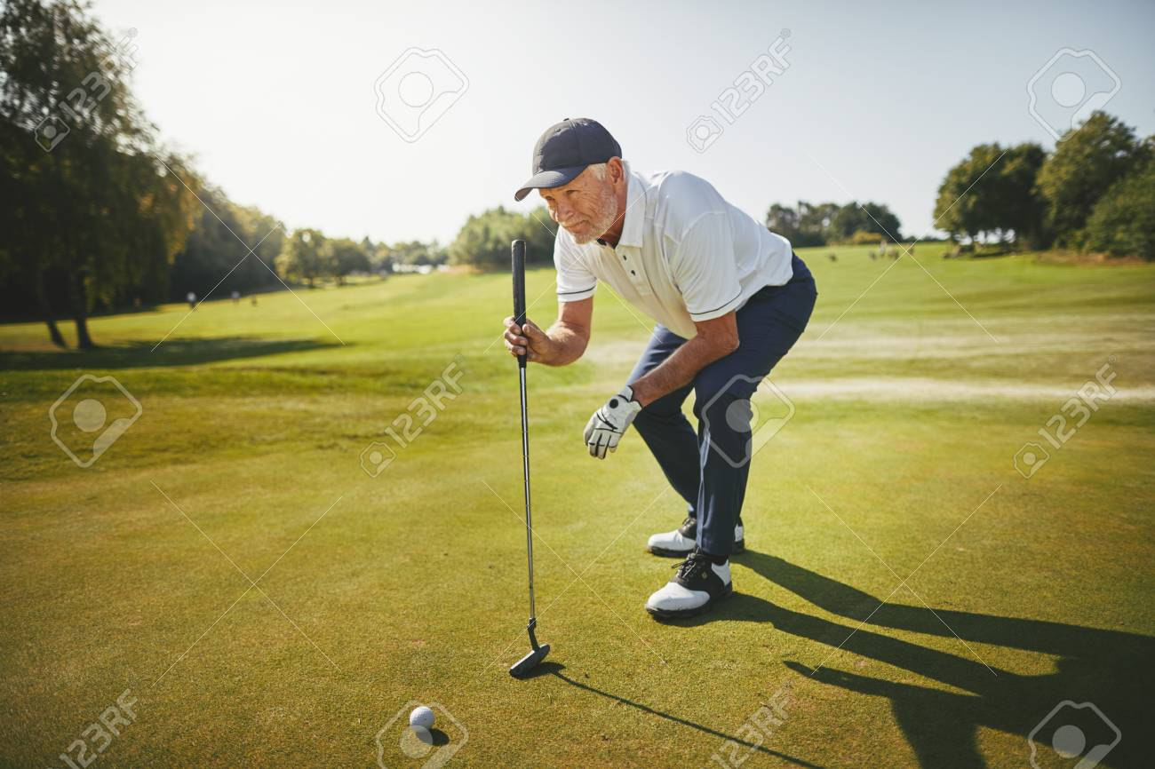 Sporty senior man crouching on a green planning his putt while enjoying a round of golf on a sunny day - 118127588