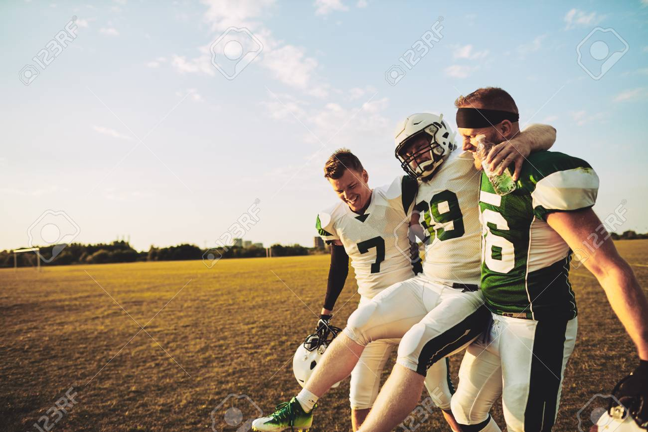 American football players carrying an injured teammate off the field during a practice session in the late afternoon - 118922147