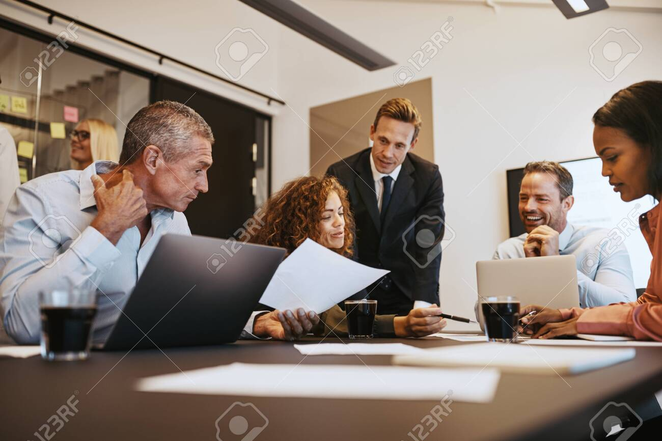Group of diverse businesspeople discussing paperwork while having a meeting together in an office boardroom - 123904839