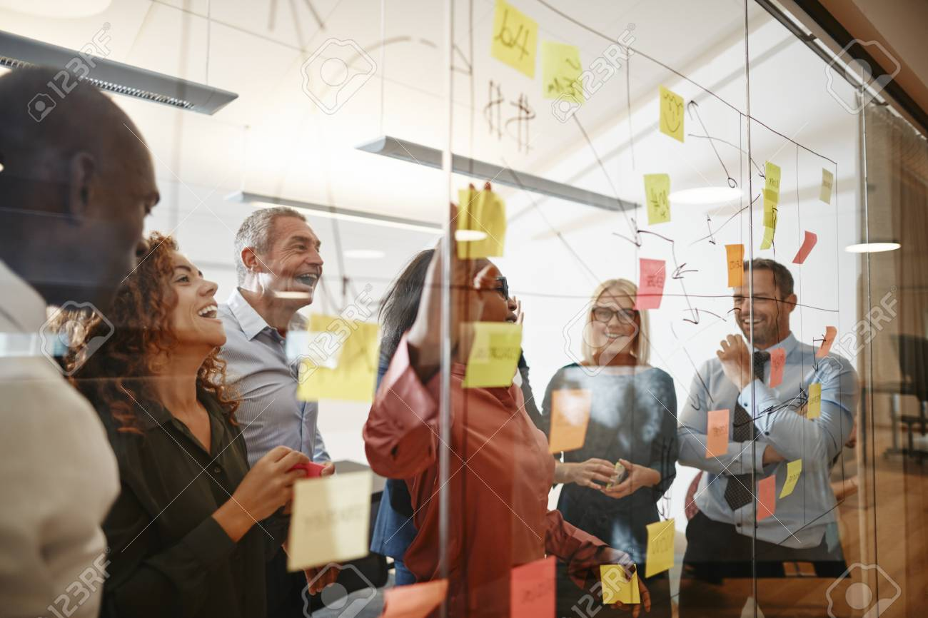 Young African businesswoman and her diverse team laughing while having a brainstorming session with sticky notes on a glass wall in a modern office - 121104733