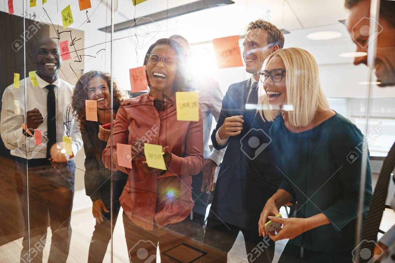 Laughing group of diverse businesspeople having a brainstorming session together with sticky notes in an office - 123904879