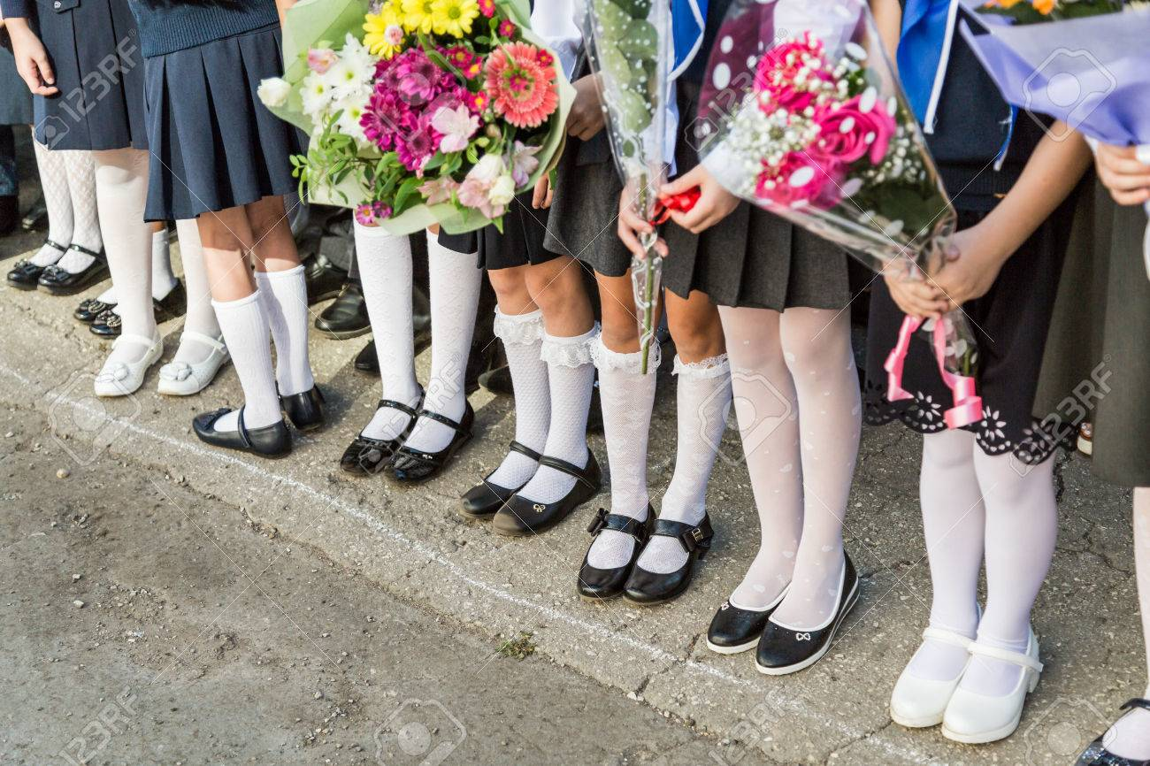 60d1304b5cf Girls primary school with bouquets of flowers in her hands. Shoes on her  feet and