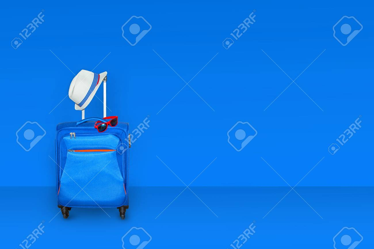 Blue suitcase with a summer hat and fashionable sunglasses isolated on white background. Summer vacation travel concept. - 97945812