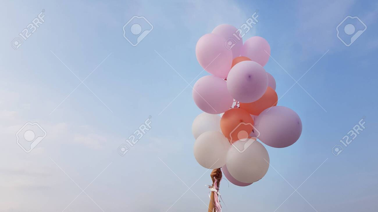 Flying balloons of delicate pink and white coral flowers in female hand on background of blue sky with clouds - 131033577