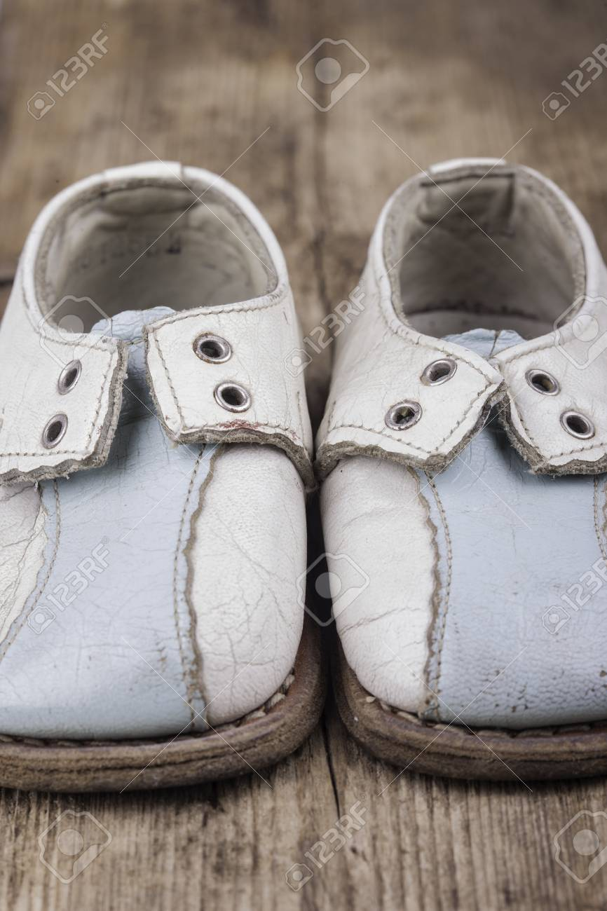 Old Vintage Baby Shoes On A Wooden