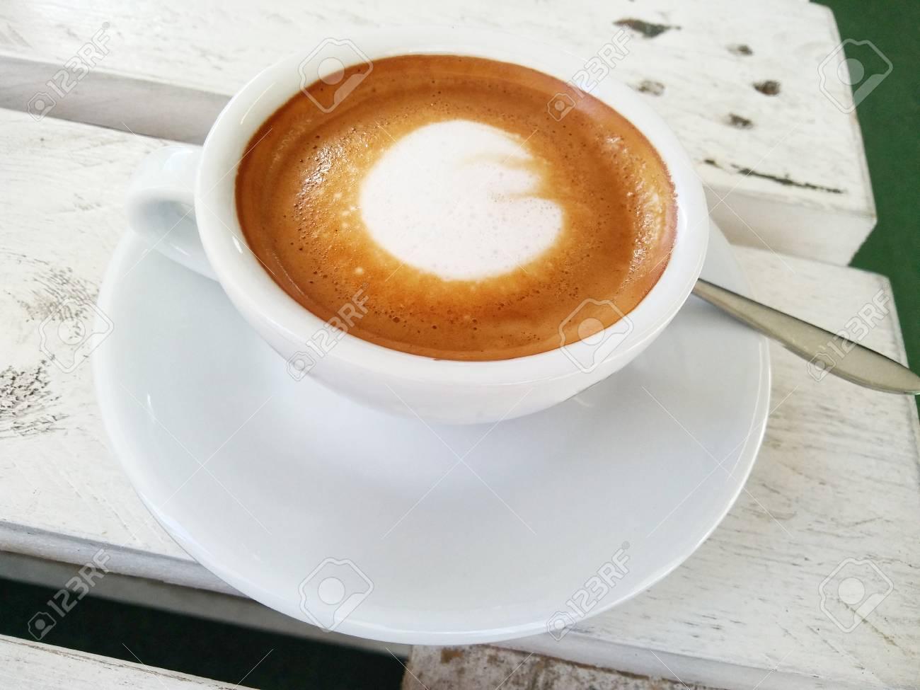 Tazza di caffè bianco con un caffè gourmet sul tavolo del bordo di