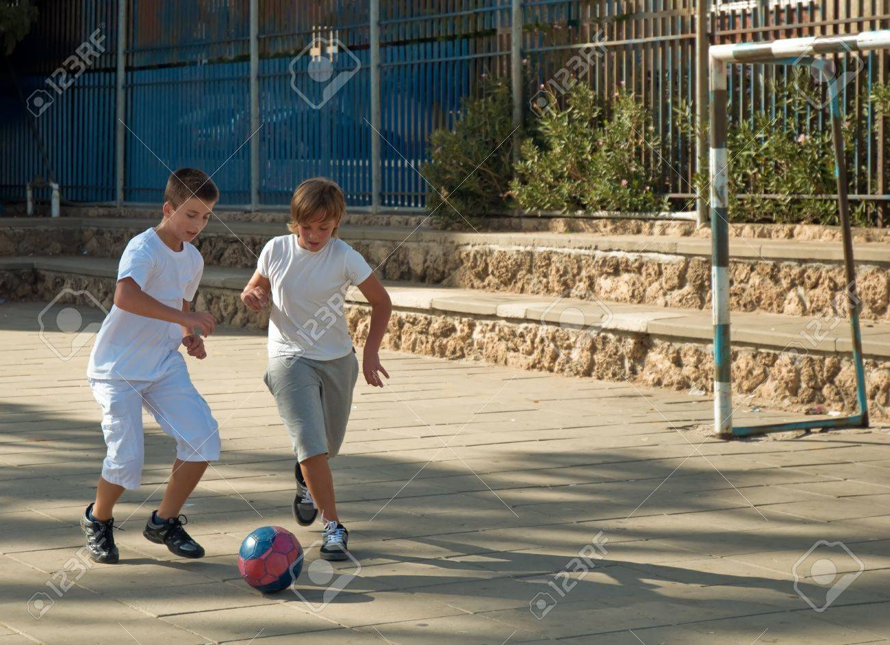Teenage boys playing soccer at sunny day . Stock Photo - 9554616