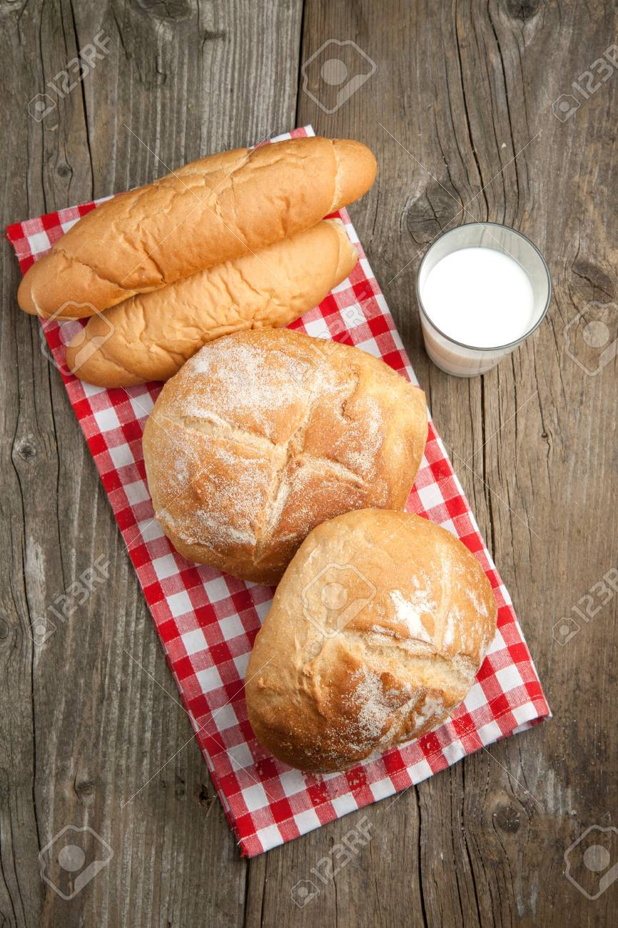 Top view on fresh bread on red and white napkin and glass of milk on old wooden table Stock Photo - 9239112