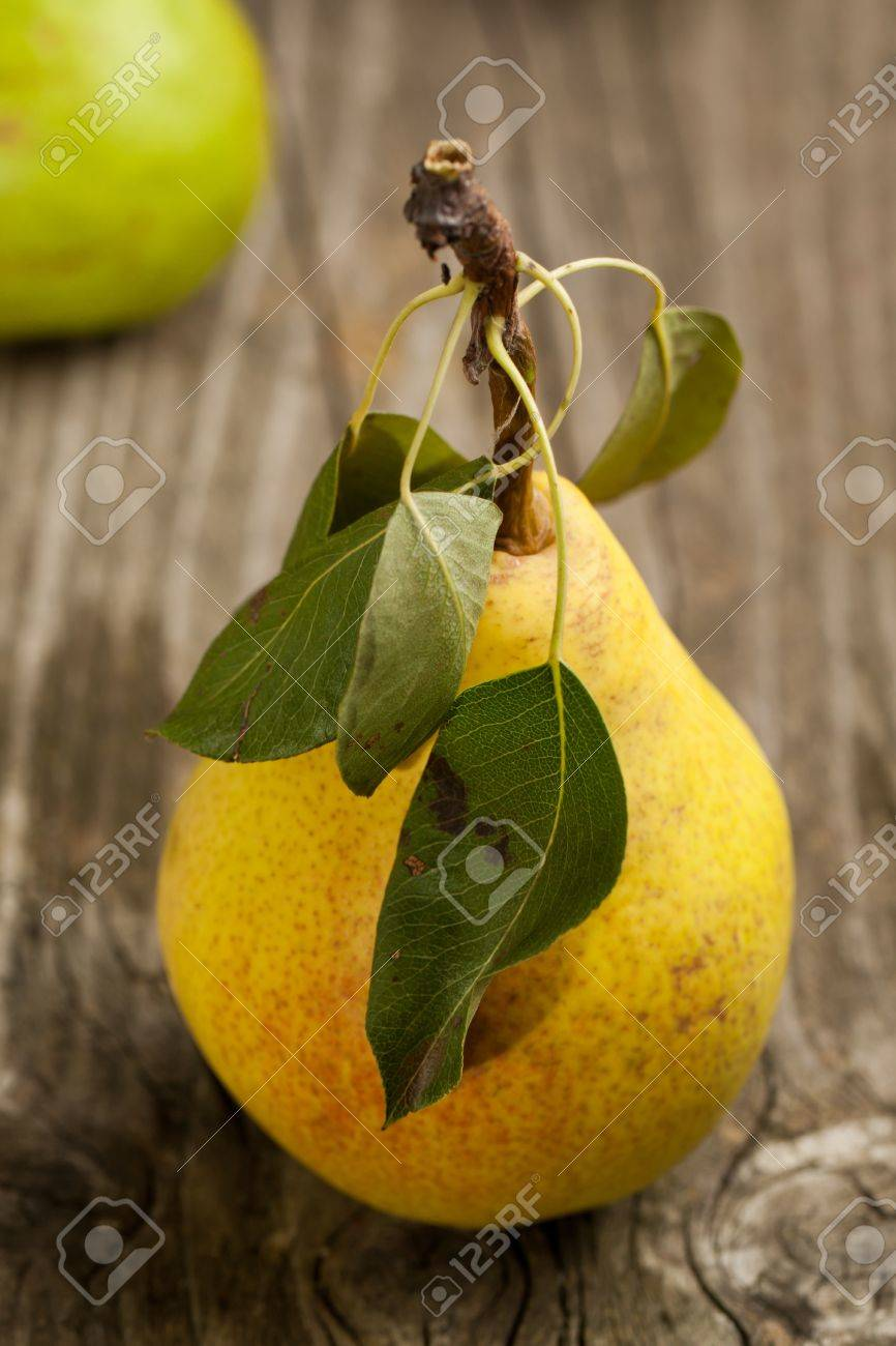 Fresh pear with leaves on old wooden table Stock Photo - 10280262