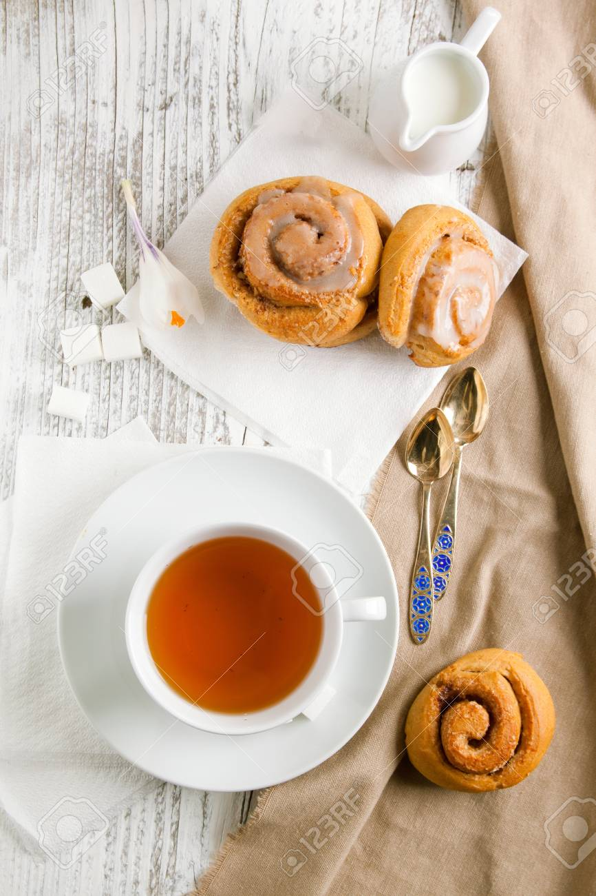 Breakfast with sweet cinnamon buns and cup of tea served on white wooden table - 12934894