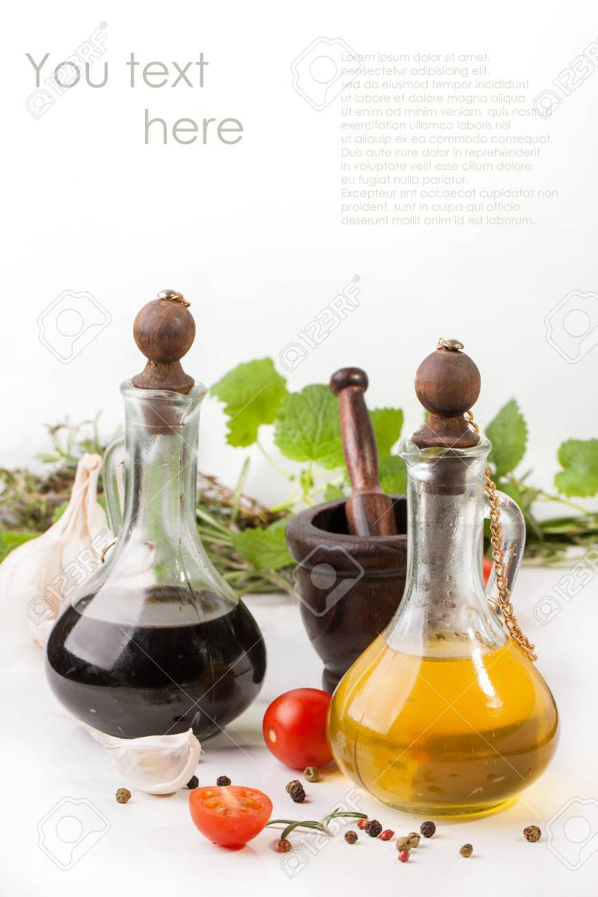 Olive oil and vinegar in vintage bottles with garlic, sliced cherry tomatoes, mint and rosemary in wooden mortar with sample text - 17926163